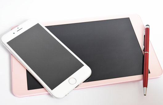 机の上に置かれたアイフォンとiPad