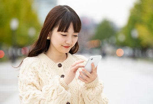 街中、スマートフォンで楽しそうに動画を楽しむ女性