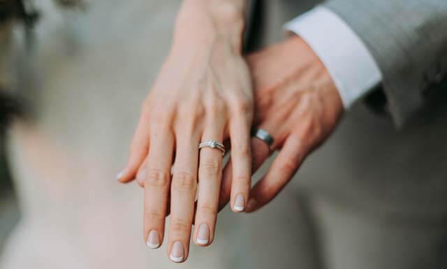 結婚指輪をはめて、2人手を乗せあった夫婦の画像